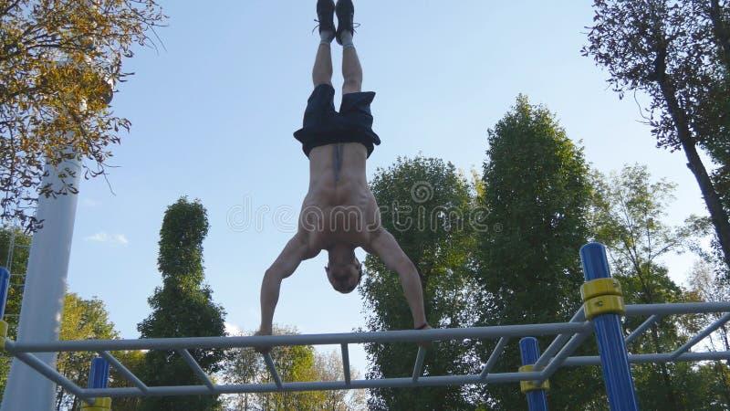 Homme musculaire fort faisant un appui renversé en parc Type masculin musculaire convenable de forme physique faisant des cascade image stock