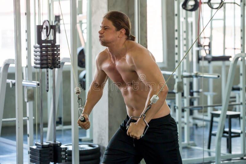 Homme musculaire pompant le coffre de muscles avec le croisement de câble au gymnase dans la lumière de matin séance d'entraîneme photographie stock