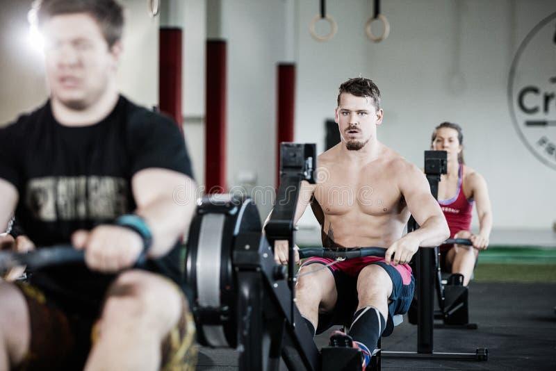 Homme musculaire s'exerçant sur la machine à ramer dans le gymnase images stock
