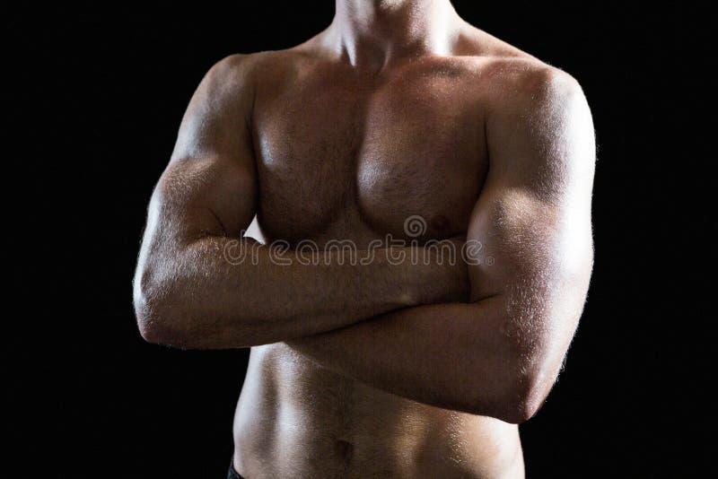 Homme musculaire sans chemise avec des bras croisés images libres de droits