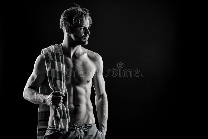 Homme musculaire sur le fond foncé avec la serviette Entretenir votre corps après séance d'entraînement dure Noir et blanc, athlè photographie stock libre de droits