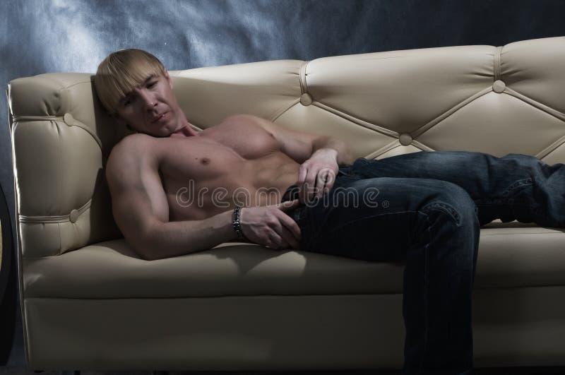 Homme musculaire sur le sofa photographie stock libre de droits