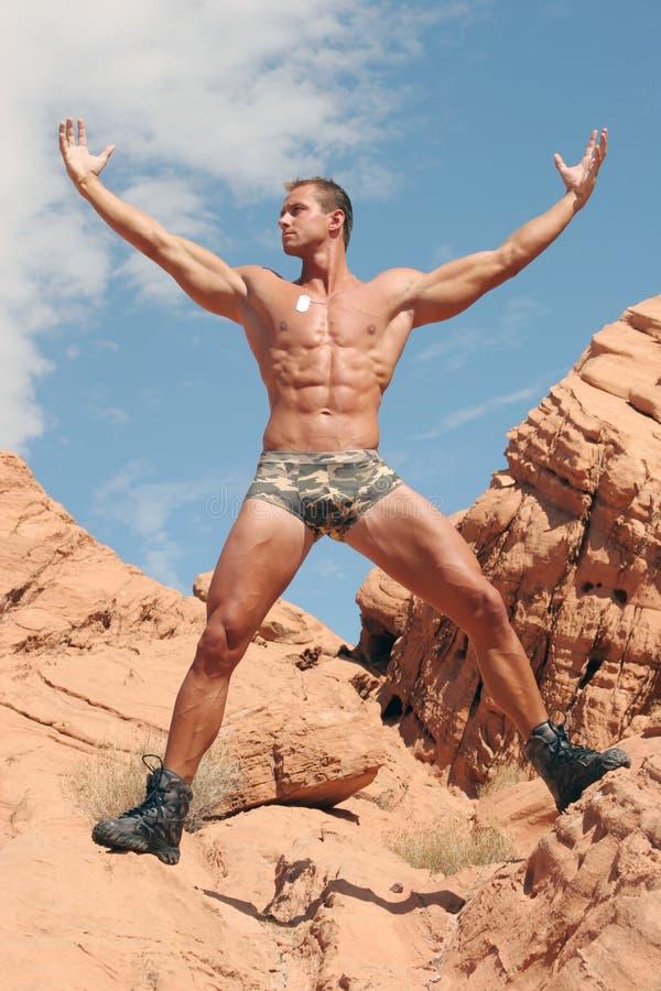 Homme musculaire sur les roches rouges photos libres de droits