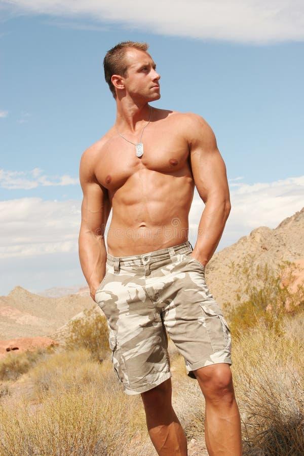 Homme musculaire sur les roches rouges photo stock
