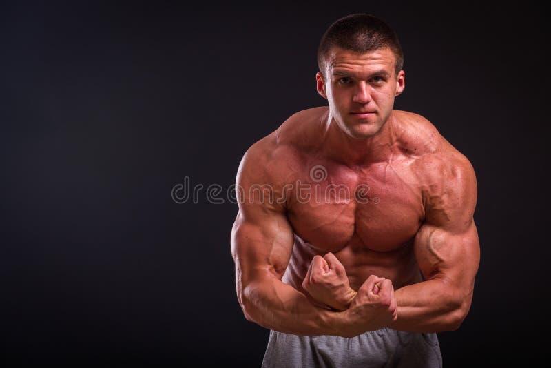 Homme musculaire sur un fond foncé photos stock
