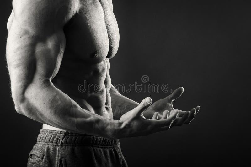 Homme musculaire sur un fond foncé image stock