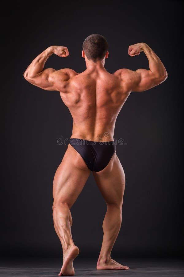Homme musculaire sur un fond foncé photographie stock