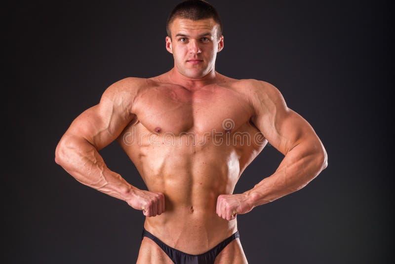 Homme musculaire sur un fond foncé images stock
