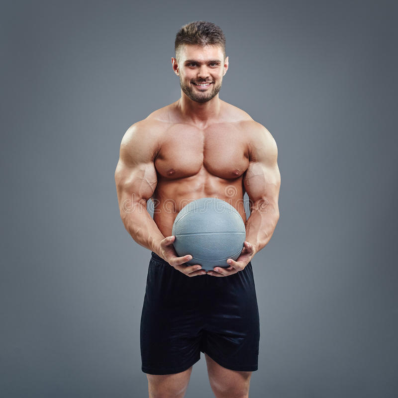 Homme musculaire tenant une boule de forme physique de médecine photographie stock
