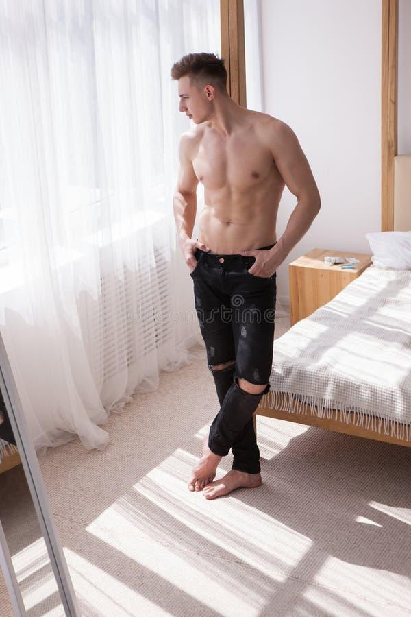 Homme musculeux bel pensant à la maison le concept photos libres de droits