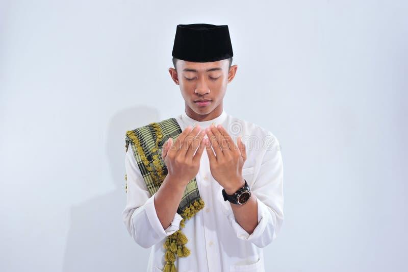 Homme musulman asiatique religieux dans la robe traditionnelle priant et faisant DUA, homme musulman asiatique utiliser le chapea image stock