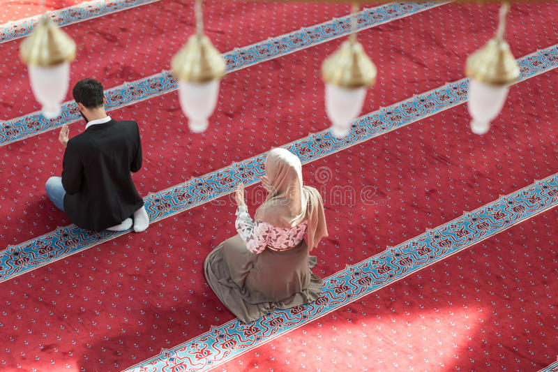 Homme musulman et femme priant dans la mosquée image libre de droits
