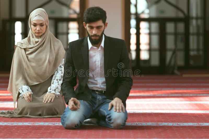 Homme musulman et femme priant dans la mosquée photographie stock