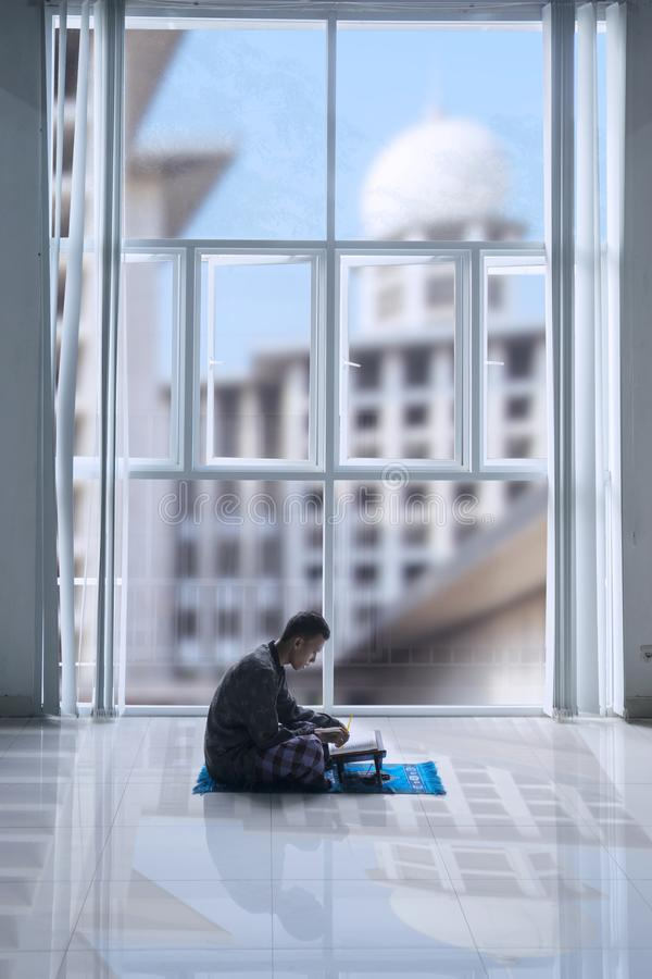 Homme musulman lisant le Quran au temps de Ramadan photos stock