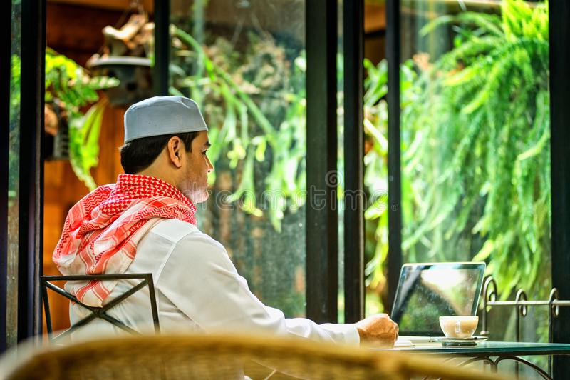 Homme musulman pakistanais d'affaires parlant sur le téléphone portable et le boire image libre de droits