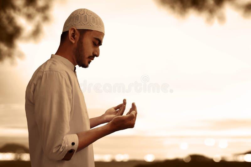 Homme musulman priant au coucher du soleil image libre de droits