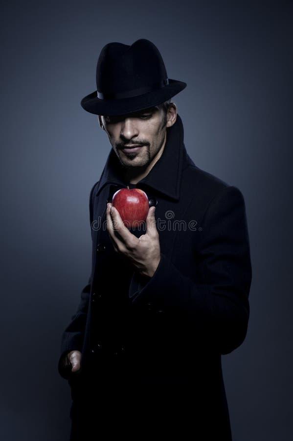 Homme mystérieux retenant une pomme photo stock