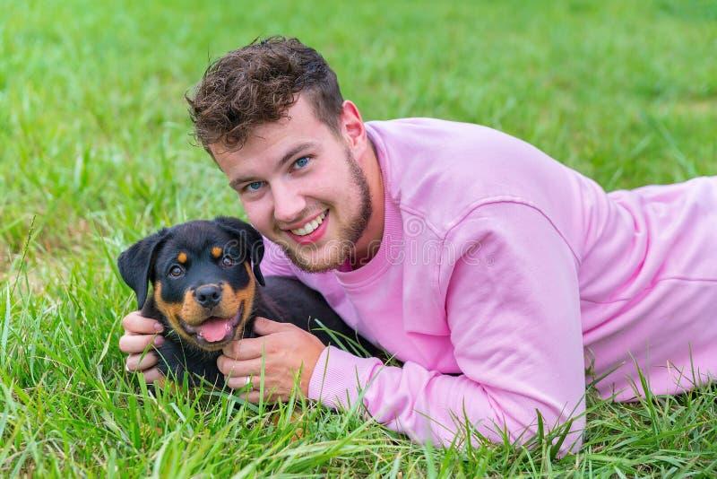 Homme néerlandais se trouvant avec le chiot de rottweiler dans l'herbe photo stock