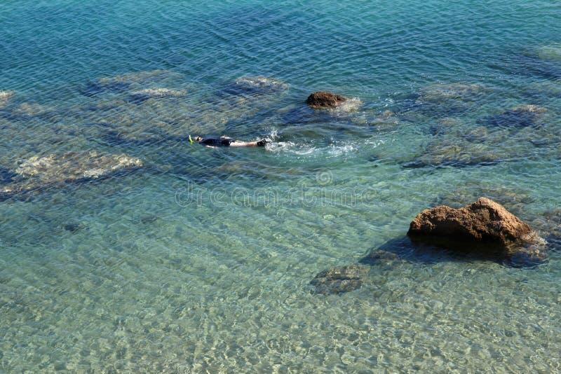 Homme naviguant au schnorchel dans l'eau clair comme de l'eau de roche photo libre de droits
