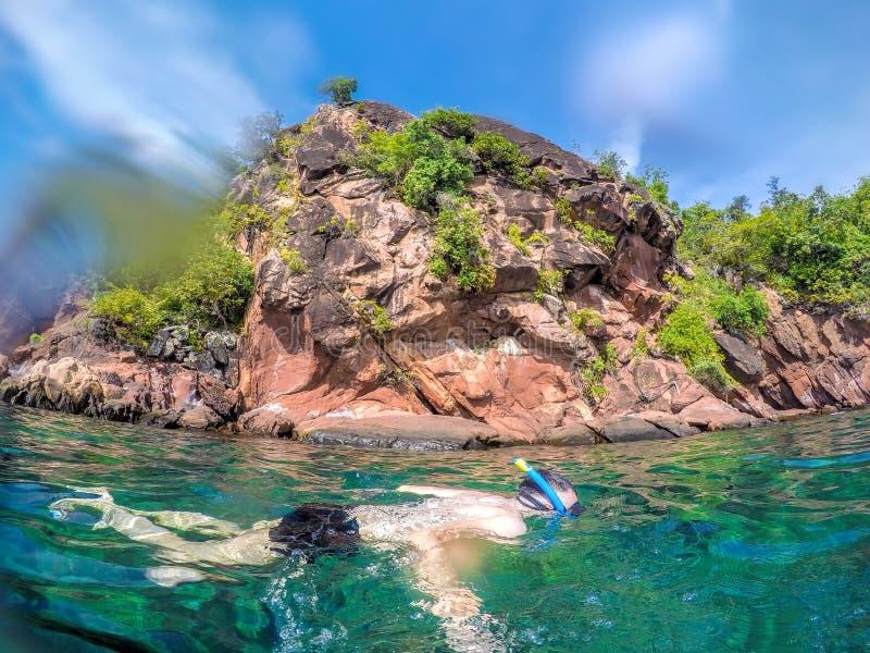 Homme naviguant au schnorchel dans l'eau clair comme de l'eau de roche en Thaïlande photo libre de droits