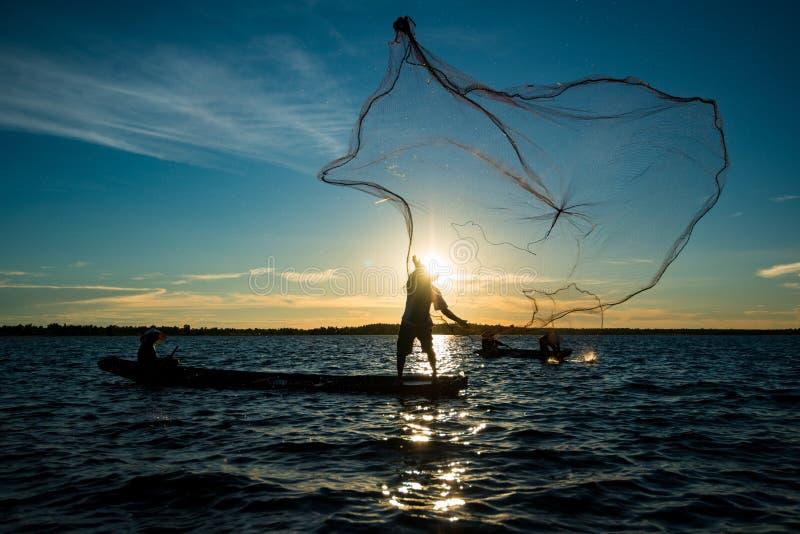 Homme non identifié de pêcheur de silhouette sur la pêche de bateau par le lancement photos stock