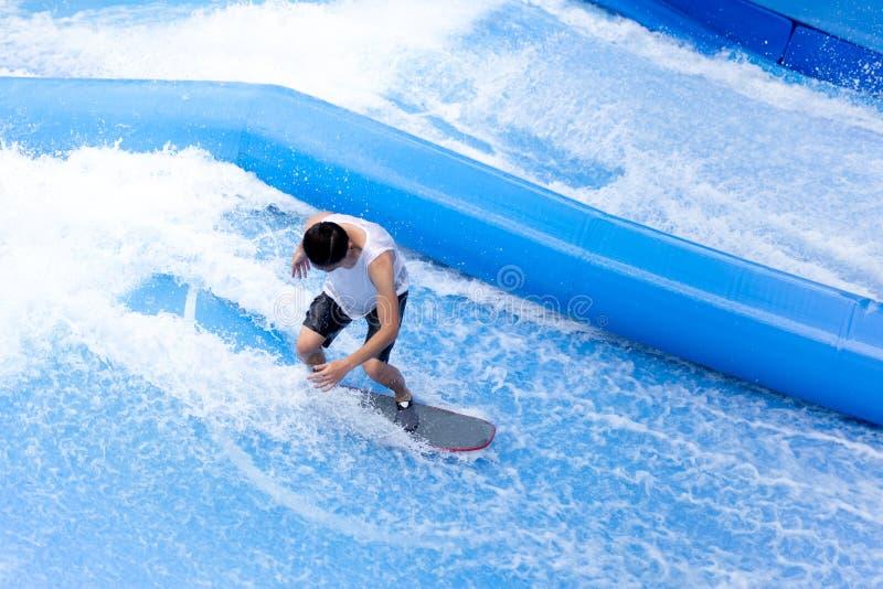 Homme non identifié jouant le sport extrême d'intérieur de planche de surf image stock
