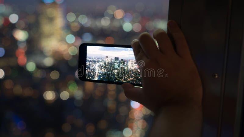 Homme non identifié prenant une photo d'horizon de Tokyo avec son téléphone intelligent de tour de Tokyo, Japon photo stock