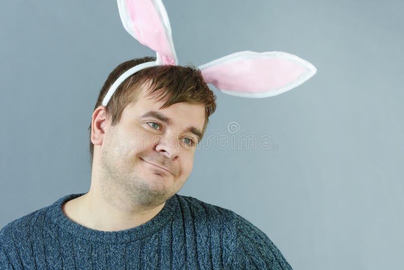 Homme non rasé avec des oreilles de lapin sur un fond gris L'homme maniaque sourit images libres de droits