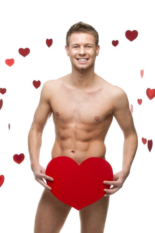 Homme nu drôle tenant le grand coeur de papier rouge image stock