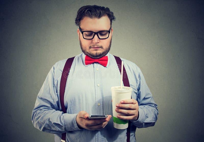 Homme obèse avec la soude et le téléphone doux images stock