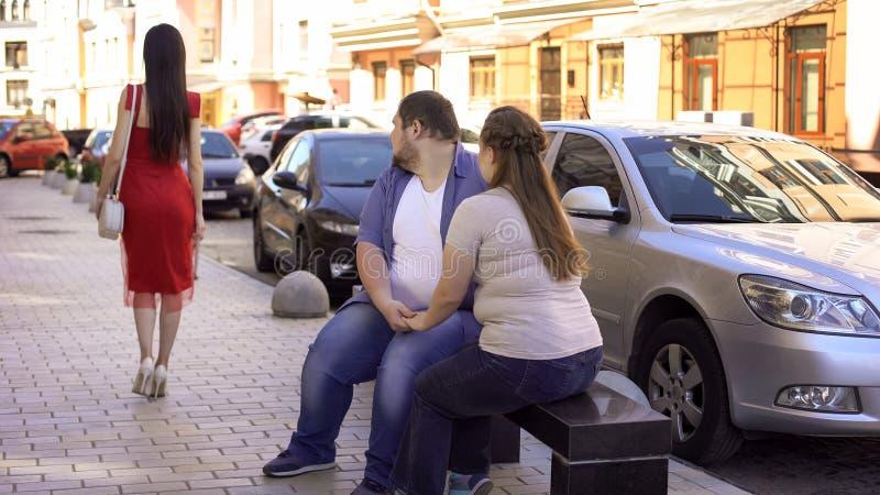 Homme obèse et femme regardant la dame mince passant par, jaloux de la forme convenable image libre de droits