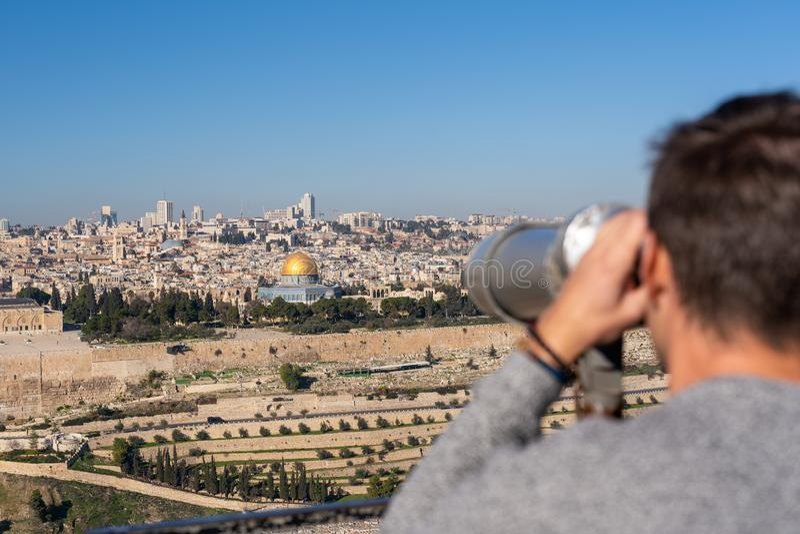 Homme observant la vieille ville de Jérusalem avec un binoculaire images stock