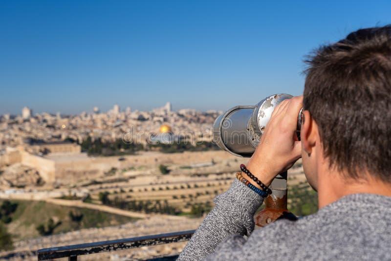 Homme observant la vieille ville de Jérusalem avec un binoculaire image stock