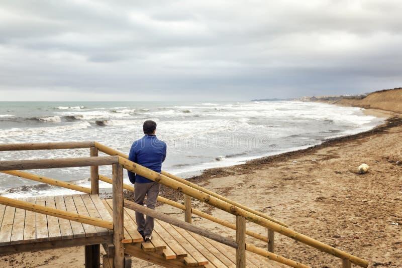 Homme observant le paysage marin de l'escalier image stock