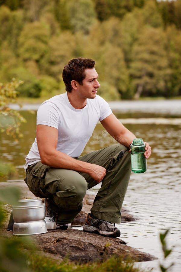 Homme obtenant l'eau image stock