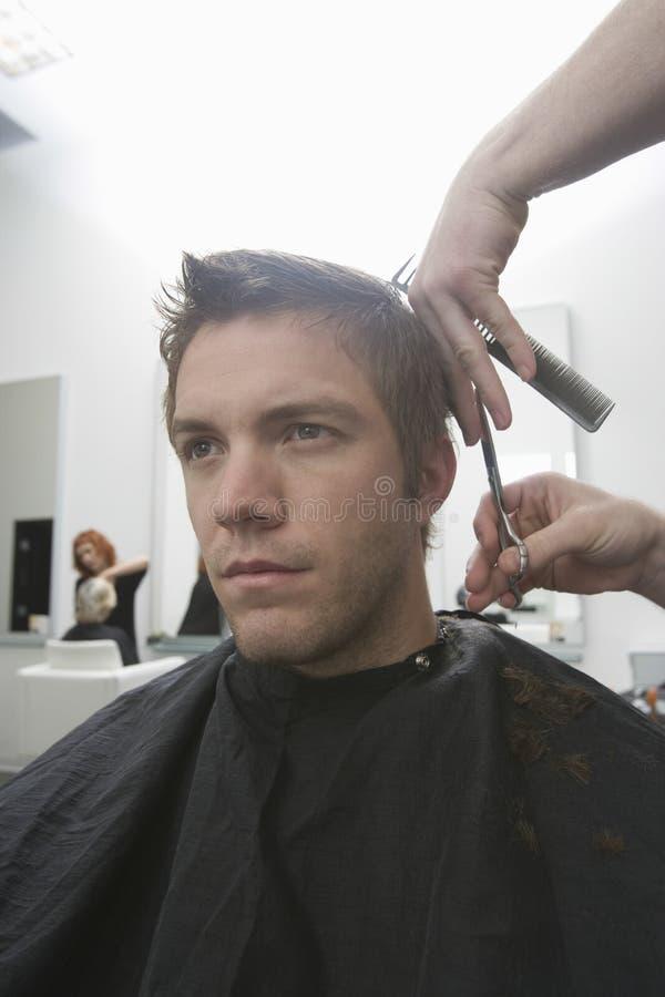 Homme obtenant la coupe de cheveux dans le salon de coiffure photo libre de droits
