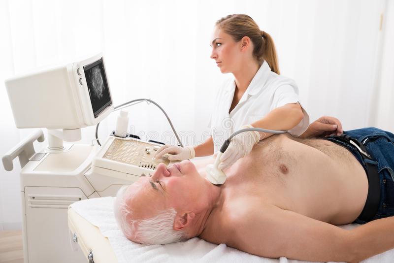 Homme obtenant le balayage d'ultrason sur le cou par le docteur photo stock
