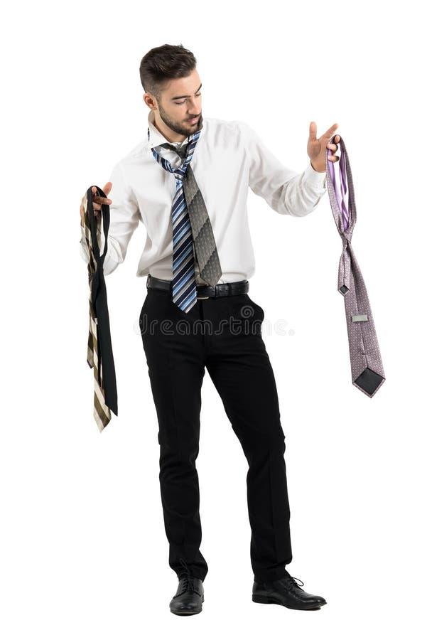 Homme obtenant le choix habillé parmi beaucoup de cravates photographie stock