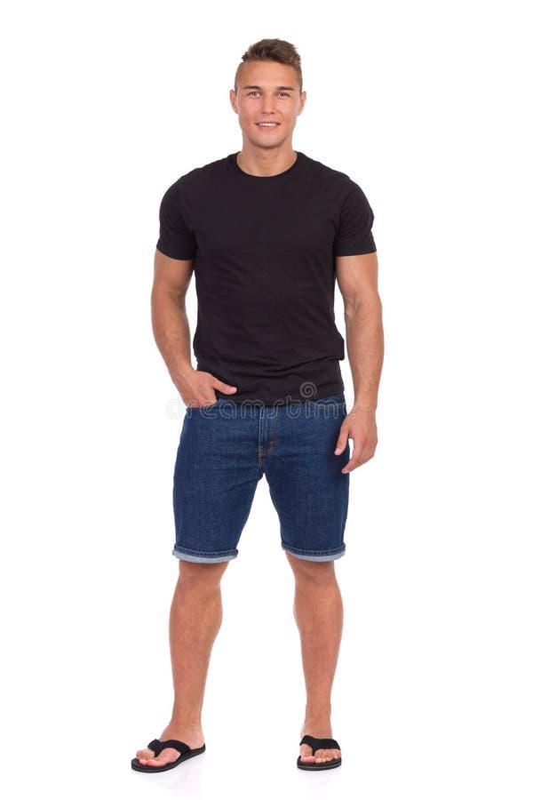 Homme occasionnel bel dans des shorts de jeans d'isolement image libre de droits