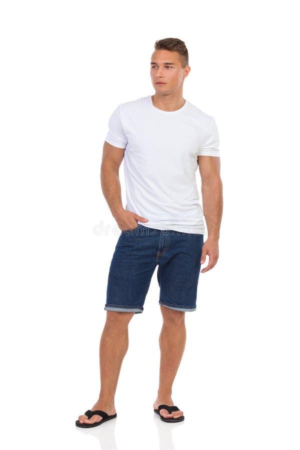 Homme occasionnel dans les shorts de jeans et le T-shirt blanc images libres de droits