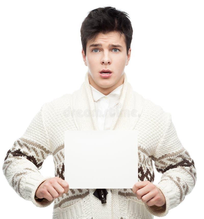 Homme occasionnel effrayé d'hiver tenant le signe photo libre de droits