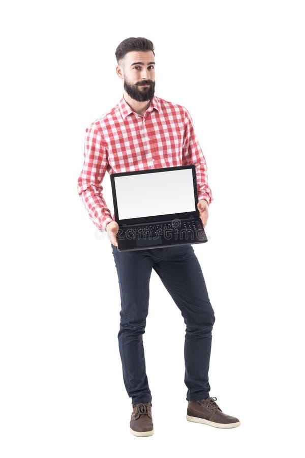 Homme occasionnel futé barbu élégant moderne présent l'affichage blanc vide d'ordinateur portable image stock