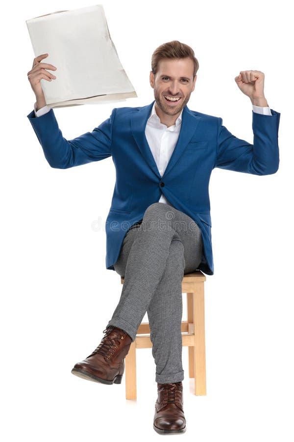 Homme occasionnel gai célébrant avec un journal dans sa main photos stock