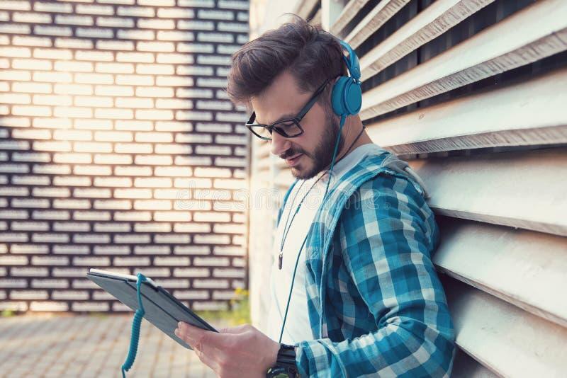 Homme occasionnel gai dans la chemise de denim et les écouteurs se tenant dehors et le comprimé surfant heureusement photos libres de droits