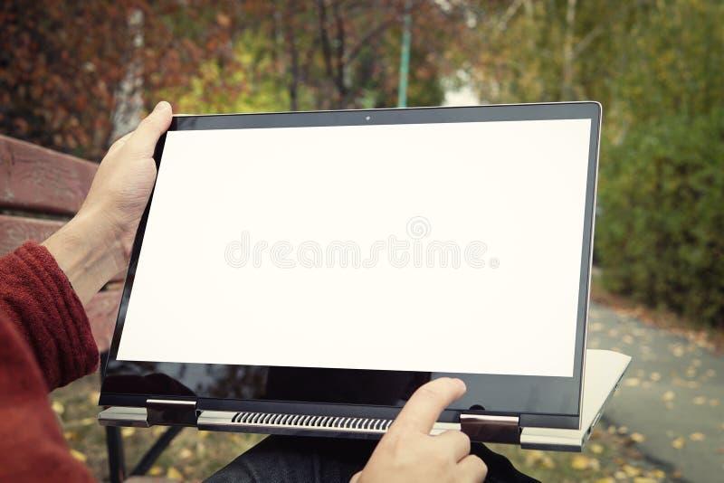 homme occasionnel s'asseyant sur un banc en parc d'automne avec ses jambes croisées et présent son ordinateur portable avec l'écr photographie stock libre de droits