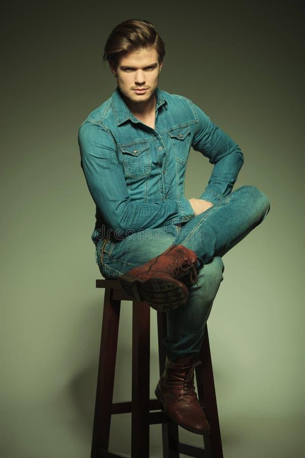 Homme occasionnel s'asseyant sur un tabouret avec ses jambes croisées photo stock