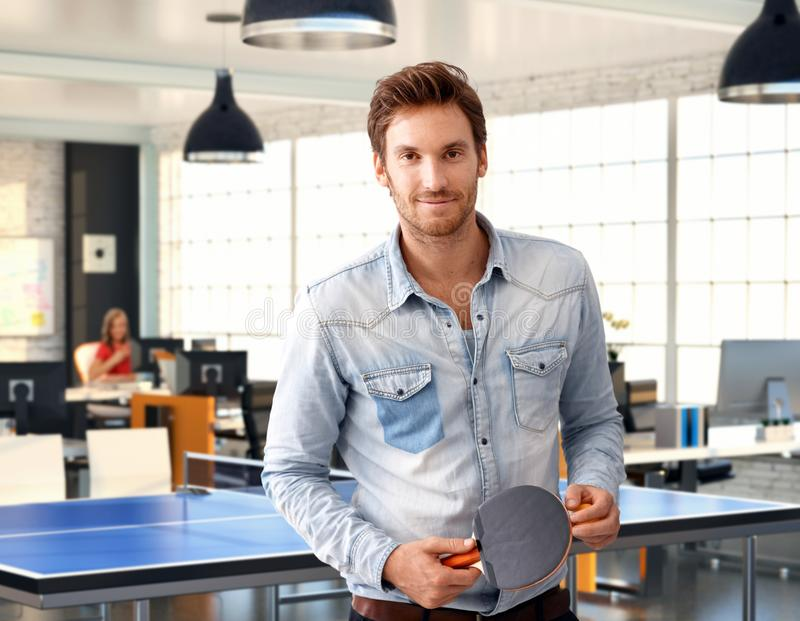 Homme occasionnel tenant la raquette de ping-pong au bureau images libres de droits