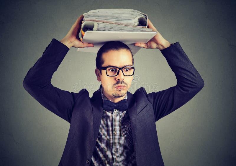Homme occupé avec le montant considérable d'écritures photographie stock