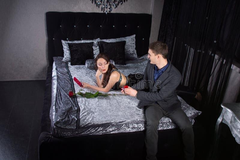 Homme offrant un anneau à l'amie à la chambre à coucher photographie stock