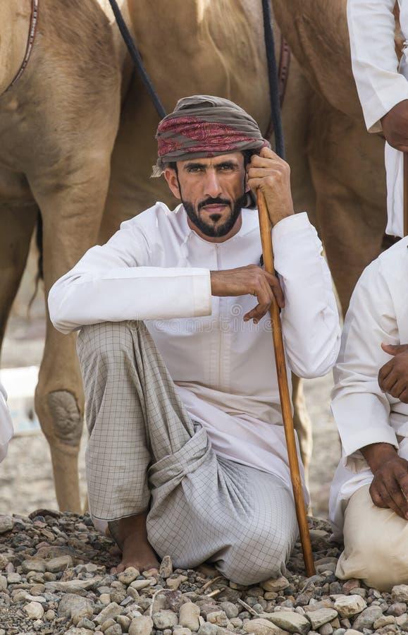 Homme omanais avec ses chameaux devant une course images libres de droits